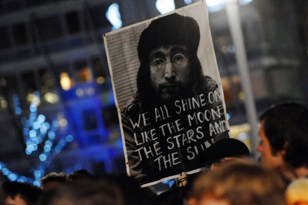 People take part in a candle lit vigil in Liverpool, north-west England on December 8, 2010 to mark the 30th anniversary ...