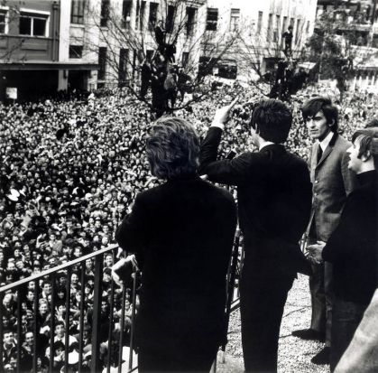 The Beatles wave to the crowd below from the balcony of the Southern Cross Hotel in Melbourne, during their Australia/NZ ...