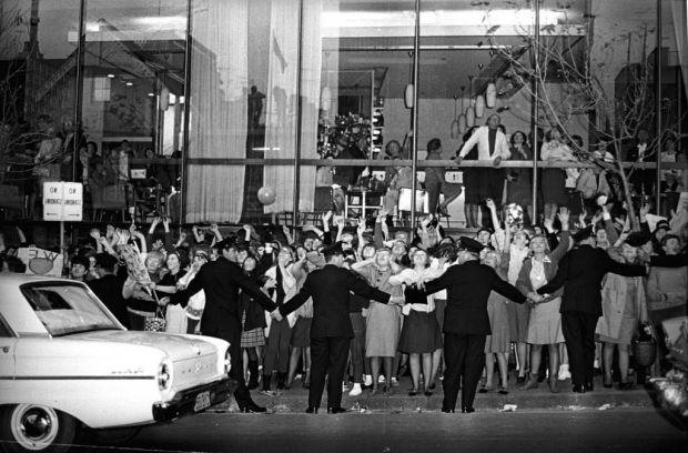Policemen hold back the tide of fans screaming for the Beatles outside the Sheraton Hotel, where they stayed in Sydney ...