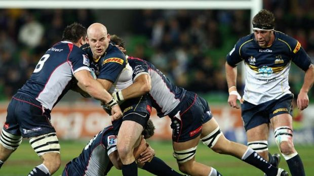 Halted, but elated .... Stephen Moore is seized upon by three Rebels players in his 50th cap for the Brumbies.