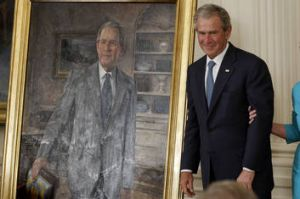 Former President George W. Bush stands next to his official portrait in the East Room at the White House.