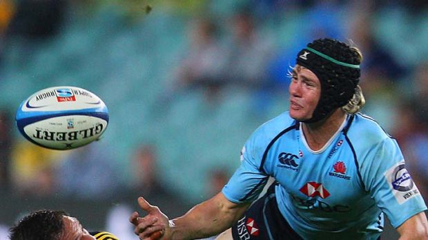 Berrick Barnes of the Waratahs passes as he is tackled.