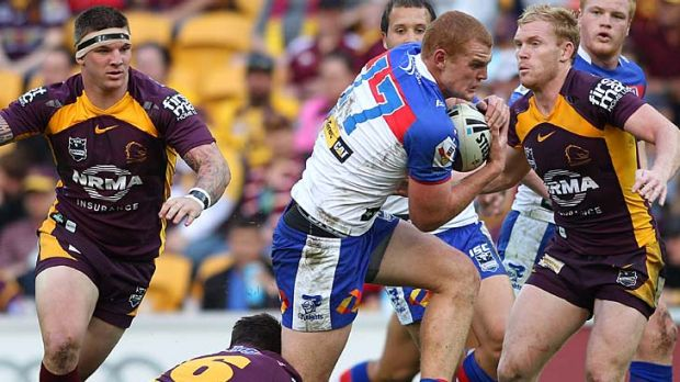 Alex McKinnon of the Knights attempts to break through the defence.