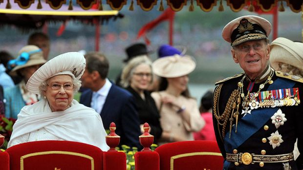 Queen Elizabeth II  and  Prince Philip watch the proceedings  from the royal barge.