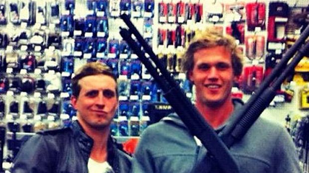 The offending image ... Nick D'Arcy and Kenrick Monk pose in a gun shop in California.