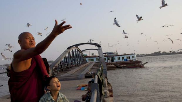 A Burmese monk and his son feed the seagulls on a jetty along the Yangon river.