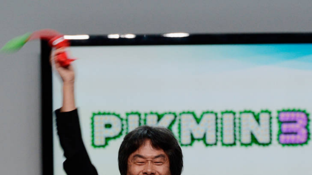 Nintendo producer Shigeru Miyamoto, who created Super Mario Bros, waves a Pikmin 3 video game character during a Wii U ...