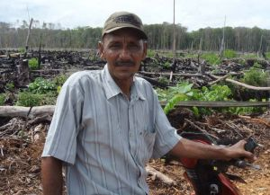 Local support ... Syukul helps plant oil palms on the burnt land.