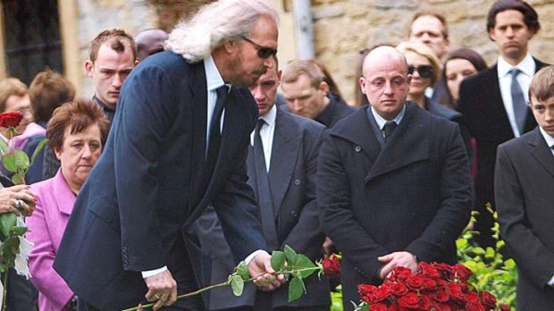 Barry Gibb places a red rose on his brother Robin's grave during the burial service in the churchyard in Thame, England.