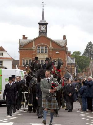 A piper leads the funeral procession of Robin Gibb though the town center of Thame, England.