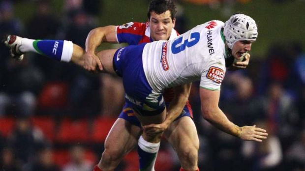 Dumped ... Jarrod Crocker of the Raiders is tackled heavily by Jarrod Mullen of the Knights.