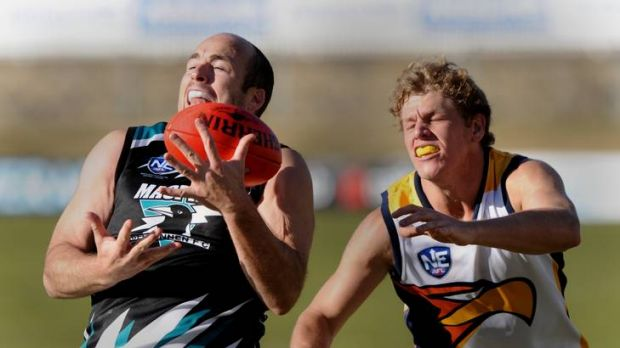 Magpies player Matthew Lokan takes mark against the Hills Eagles at Manuka Oval.