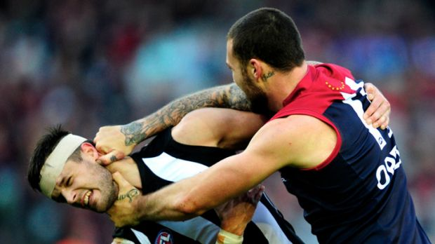 Demon Mitch Clark comes to grips with Collingwood defender Nathan Brown.