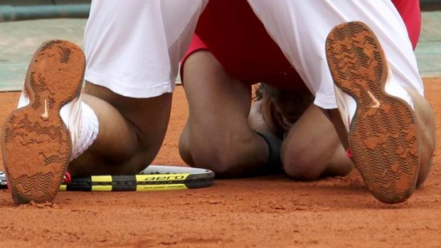 Clay king ... Rafel Nadal drops to his knees after defeating Novak Djokovic to secure a record seventh French Open win.