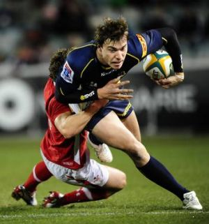 Brumbies player Cam Crawford is tackled by a Welsh defender.