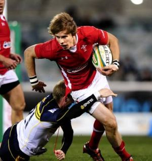 Brumbies player, Tom Cox trys to tackle Wales player, Liam Williams.