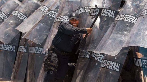 Bringing down barriers … an instructor pushes on the shields of riot police training to provide security for the ...