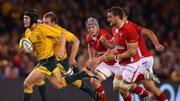 Catch me if you can: Wallaby Berrick Barnes makes a break and leads a chasing pack last night.