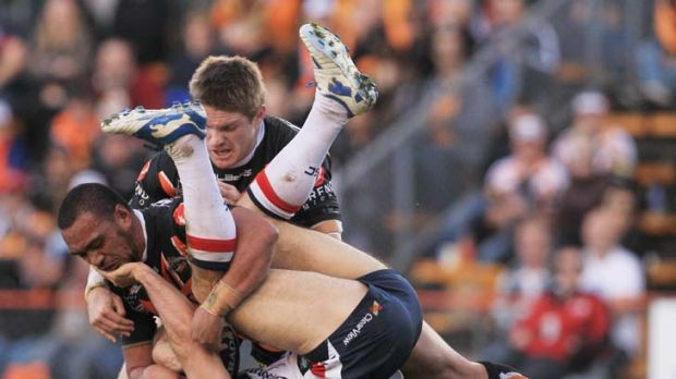 Upended … Anthony Minichiello gets mauled by Tigers.