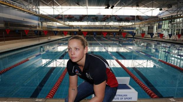 Australian women's water polo captain Kate Gynther sits on the empty AIS pool deck.