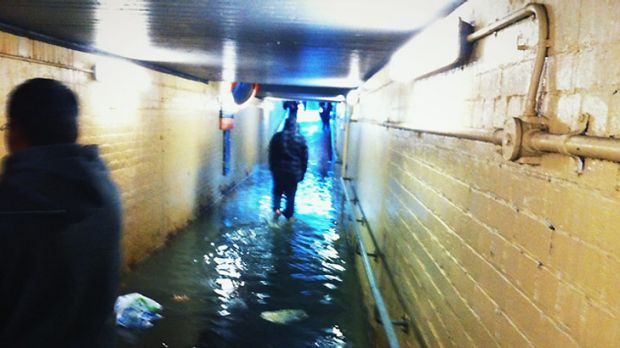 Commuters wade through the flooded tunnel.