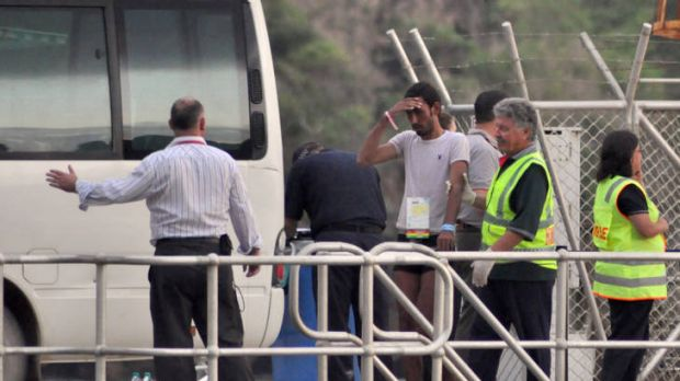 Rescued suspected asylum seekers arrive at Christmas Island after their boat capsized earlier this week.