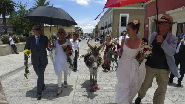 Michael Shmith (left) joins the bride who is leading her celebratory donkey.