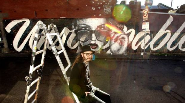Street artist Rone and one of his latest works, <i>Unstoppable</i>, in Fitzroy. His pieces bob up across Melbourne's ...