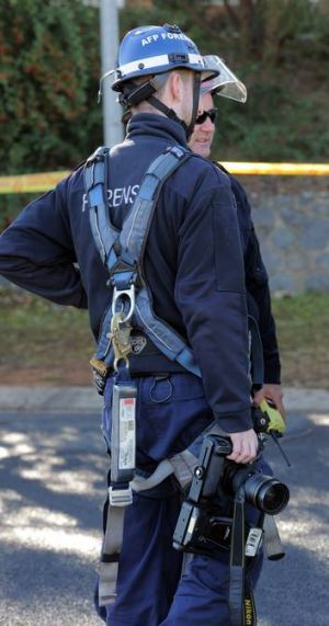An AFP Forensic staffer with camera, about to photograph the scene from the ACT Fire and Rescue Bronto.