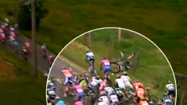 Tour tangle ... Simon Gerrans, with his legs in the air, crashes into a barbed wire fence in a bruising third stage.