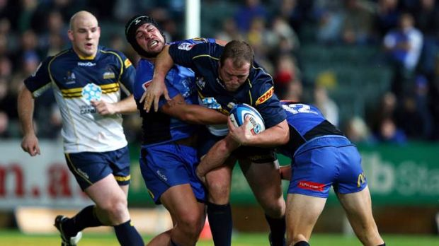 Purpose, cohesiveness and pace ... Ben Alexander of the Brumbies is tackled by the Force.