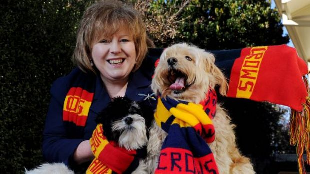 Libraries ACT director Vanessa Little with her two dogs  Wally, left,  and  Harvey in there Adelaide Crows scarfs.