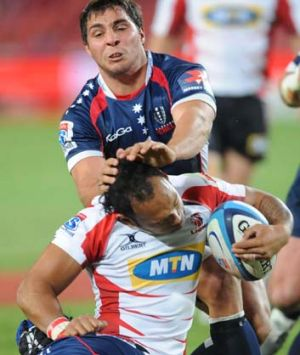 James Kamana of the Lions is tackled by Nick Phipps of the Rebels.