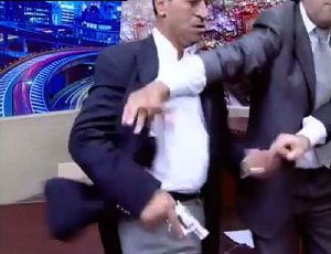 In a rage ... Jordanian MP Mohammad Shawabka pulls his pistol out.