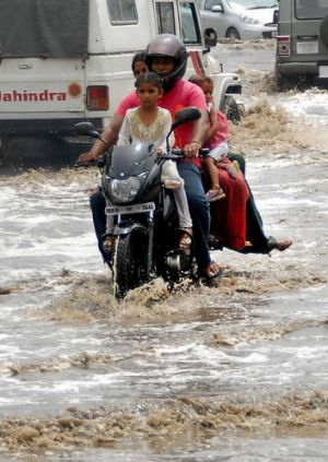 A motor-cyclist and his passengers travel along a water-logged road as the first monsoon rains arrive in Jalandhar on ...
