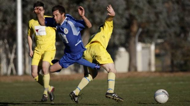 Canberra Olympic's Robbie Deeley gets fouled by Canberra City's Jonathan Bills.