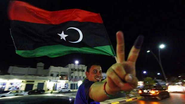 A man, with an inked finger, flashes the victory sign as he celebrates with the new Libyan flag at the end of voting day ...