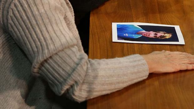 A picture of Thomas lies by the hand of his distraught mother during today's briefing.