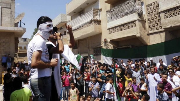 Demonstrators hold opposition flags during a protest against Syria's President Bashar al-Assad in Hama on July 6.