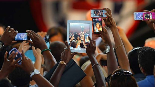 Screen queen … Michelle Obama is filmed and recorded by supporters at a high school in Florida while on the ...