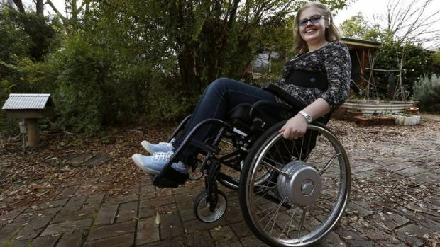 Hannah Coleman does a wheelie in her wheel chair out the front of her Kaleen Home