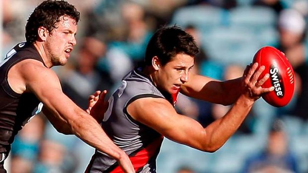 Glimmer of stardom: Essendon debutant Mark Baguley keeps the ball from Travis Boak.
