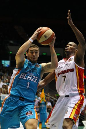 Happier times... Adam Gibson of the Gold Cast Blaze drives past Ron Dorsey of the Melbourne Tigers.