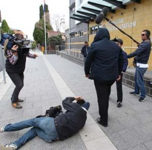 Unconscious … Channel Nine cameraman Mario Conti on the footpath after being attacked outside court yesterday.