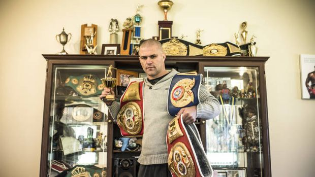 Belted … showing off the trappings of his victories at his parents' house earlier this month.