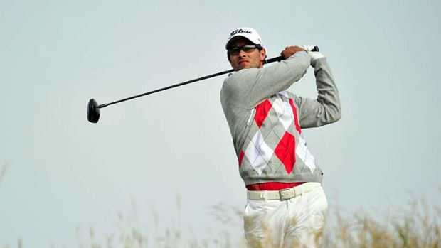 The leader ... Adam Scott of Australia watches his shot from the 11th tee during his third round on day three of the ...