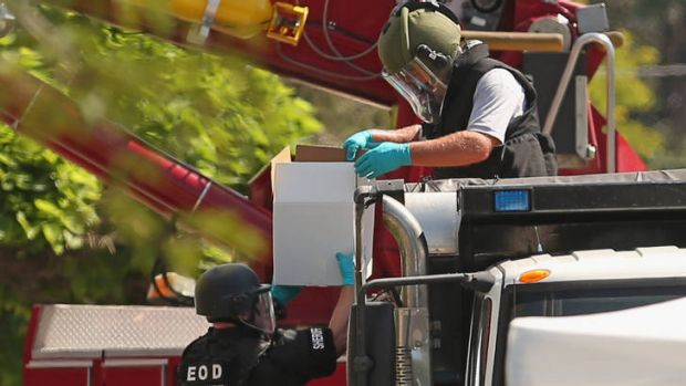 Explosives experts load boxes of improvised explosive devices removed from James Holmes' apartment into a sand-filled ...