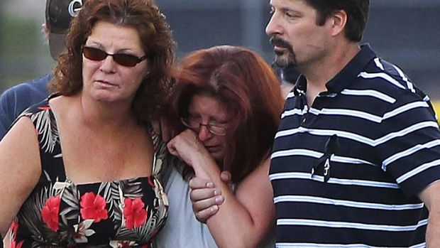 Aftermath … the mother of 18-year-old AJ Boik, who died in the shooting, is supported after a memorial for her son.