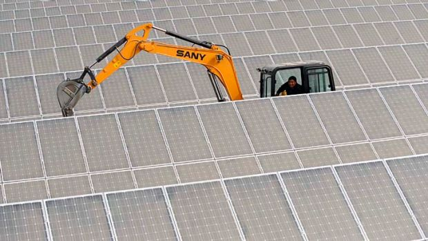 An excavator works among solar panels at a plant in China.