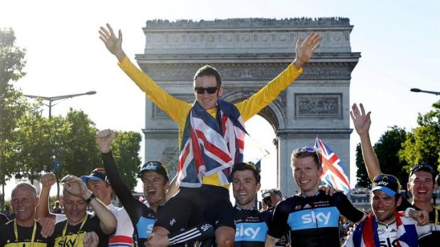 Long road to victory ... Bradley Wiggins is held aloft by his teammates as they celebrate in front of the Arc de Triomphe.